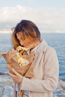 Retrato de mulher bonita em pé e cheirando as flores na beira-mar durante o dia.