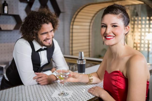 Retrato de mulher bonita em pé no balcão de bar