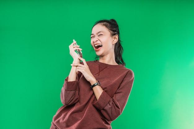 Retrato de mulher bonita está falando ao telefone com alguém, expressão rir felizmente isolada contra o fundo verde