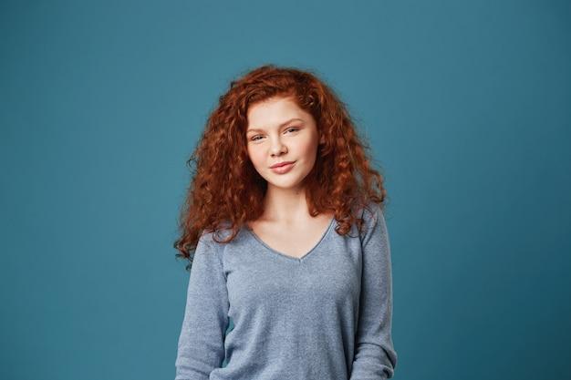Retrato de mulher bonita estudante com cabelos cacheados ruivos e sardas olhando com expressão calma e relaxada.