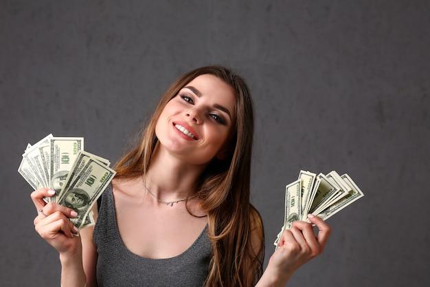 Retrato de mulher bonita europeu. espalhando dinheiro notas de dólares em moda promete estilo encaracolado
