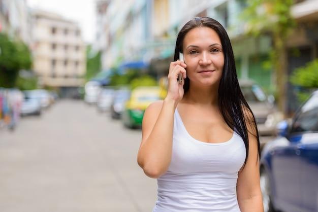 Retrato de mulher bonita falando ao telefone ao ar livre