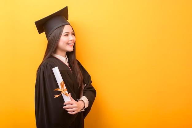 Retrato de mulher bonita feliz em vestido de formatura está segurando o certificado de educação em fundo amarelo