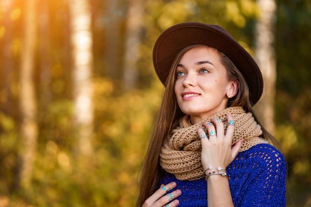 Retrato de mulher bonita feliz morena pensativa outono com cabelos longos, com um chapéu marrom e uma camisola de malha com scart quente ao ar livre no outono