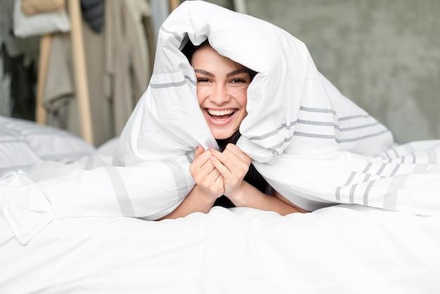 Retrato de mulher bonita feliz na cama