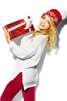 Retrato de mulher bonita feliz sorridente mulher loira doce segurando nas mãos grande caixa de presente de natal em roupas de inverno casual vermelho hipster, em camisola quente branca