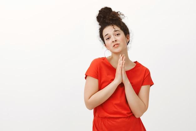 Retrato de mulher bonita gananciosa com cabelo encaracolado em um vestido vermelho, orando de mãos dadas com as palmas das mãos juntas sobre o peito, implorando por favor ou ajuda