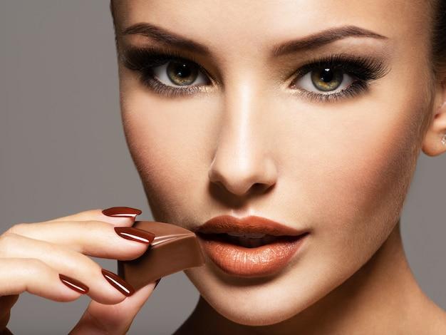 Retrato de mulher bonita glamour detém e come doces de chocolate. foto no estilo marrom