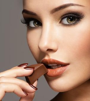 Retrato de mulher bonita glamour detém e come doces de chocolate.
