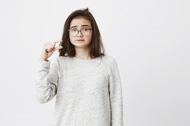 Retrato de mulher bonita infeliz com óculos mostrando algo pequeno ou pequeno