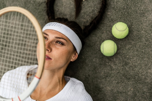 Retrato, de, mulher bonita, jogando tênis, ao ar livre