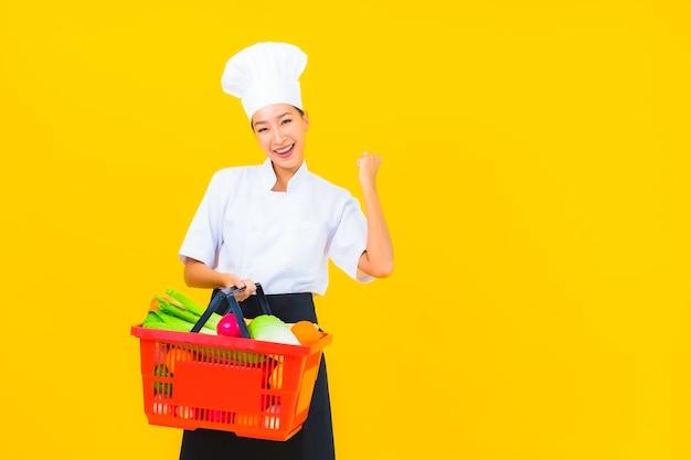 Retrato de mulher bonita jovem chef asiática com cesta de supermercado em fundo amarelo isolado