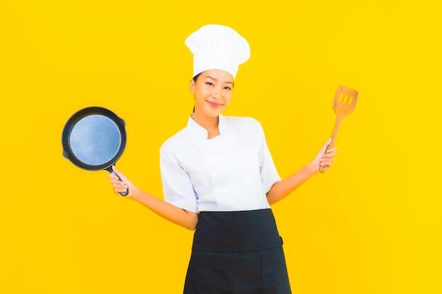 Retrato de mulher bonita jovem chef asiática com panela preta sobre fundo amarelo isolado.