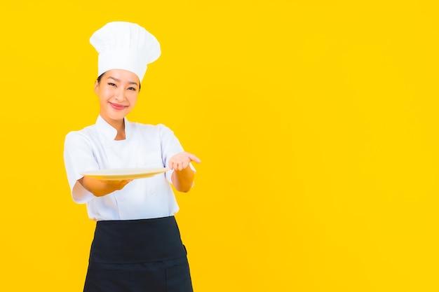 Retrato de mulher bonita jovem chef asiática com placa em fundo amarelo isolado.