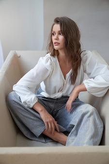Retrato de mulher bonita jovem elegante vestindo camisa branca fasionable e calças largas, posando na banheira