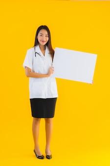 Retrato de mulher bonita jovem médico asiático com placa branca vazia