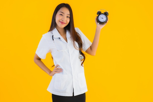 Retrato de mulher bonita jovem médico asiático mostra despertador