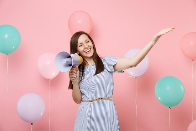 Retrato de mulher bonita jovem sorridente num vestido azul, segurando o megafone, apontando a mão de lado no fundo rosa com balões de ar coloridos. festa de aniversário, conceito de emoções sinceras de pessoas.