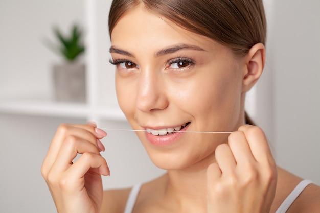 Retrato de mulher bonita, limpando os dentes com fio dental. Foto Premium