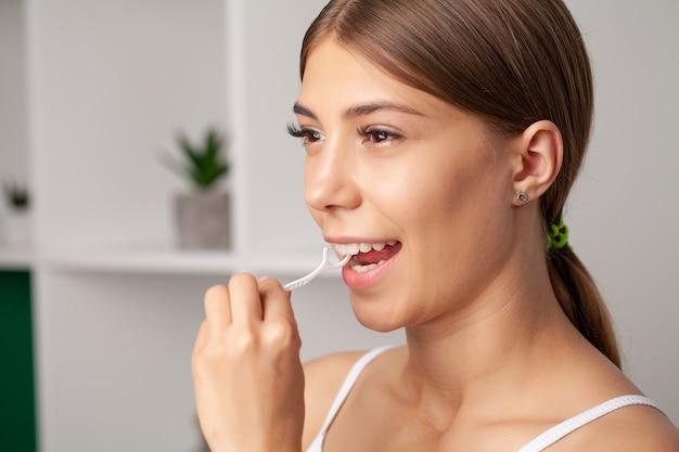 Retrato de mulher bonita, limpando os dentes com fio dental.
