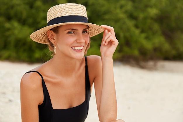 Retrato de mulher bonita magro tem aparência atraente, expressão feliz, usa roupas de verão, posa na praia arenosa contra vegetação tropical verde, tem férias idílicas ou resort. conceito de estilo de vida