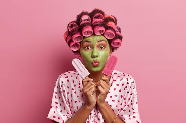 Retrato de mulher bonita mantém os lábios arredondados, aplica máscara facial verde, enroladores de cabelo, segura dois deliciosos sorvetes, vestida com vestido de seda