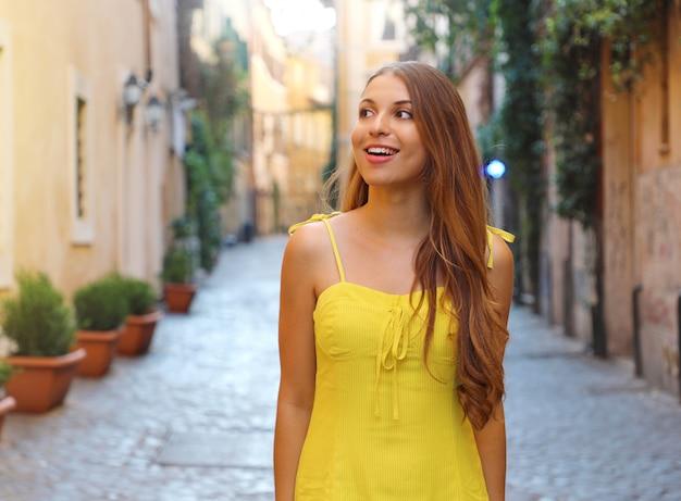 Retrato de mulher bonita moda com cabelo comprido em vestido de verão amarelo andando e explorando o bairro de trastevere, em roma, itália.