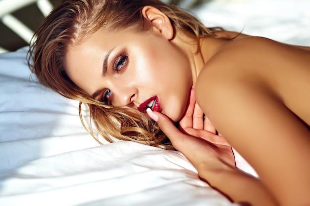 Retrato de mulher bonita na cama de manhã