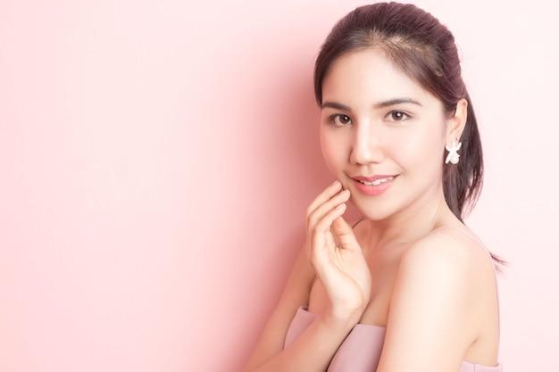 Retrato de mulher bonita na parede rosa