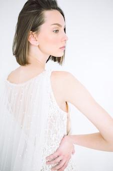 Retrato de mulher bonita na sala de pé e olhando no vestido branco longo