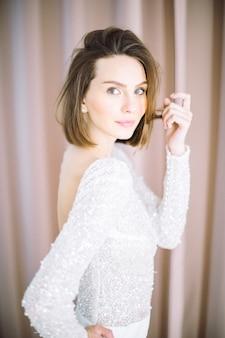 Retrato de mulher bonita no quarto com pérola em pé e olhando em calças e camisa branca