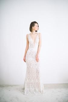 Retrato de mulher bonita no quarto em pé no vestido branco longo