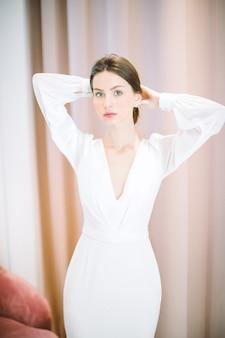 Retrato de mulher bonita no quarto pérola em pé e segurando o cabelo em vestido longo branco
