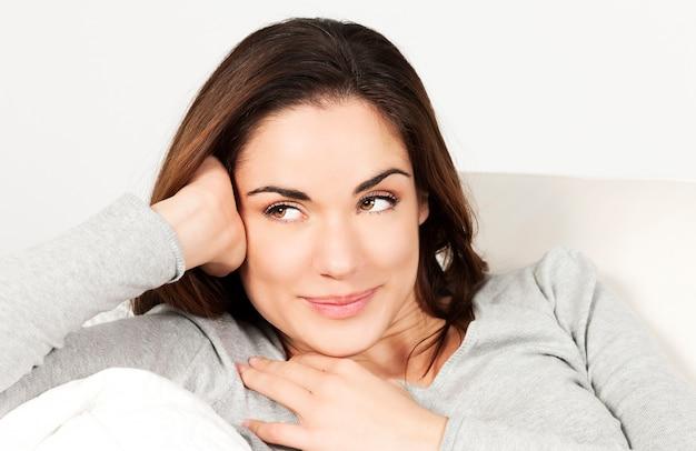 Retrato de mulher bonita no sofá em casa