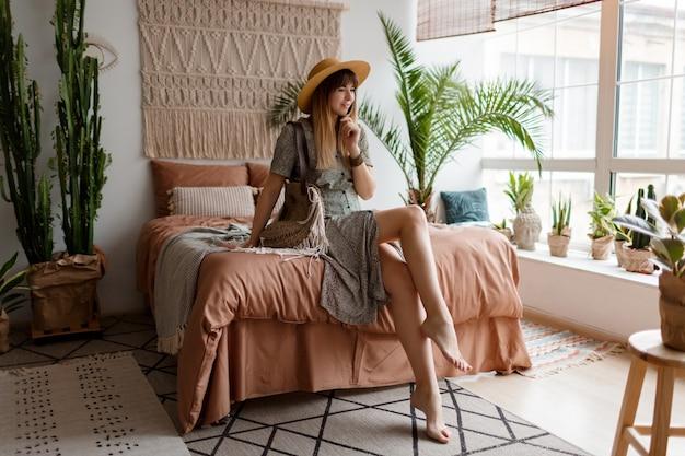 Retrato de mulher bonita no vestido, desfrutando de casa aconchegante