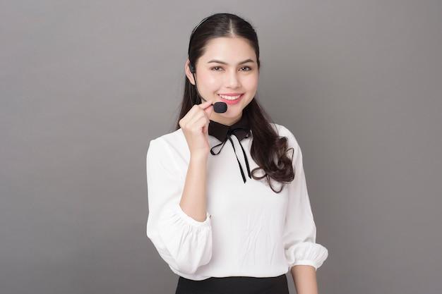 Retrato de mulher bonita operador em fundo cinza