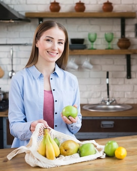 Retrato de mulher bonita, orgulhosa de frutas orgânicas
