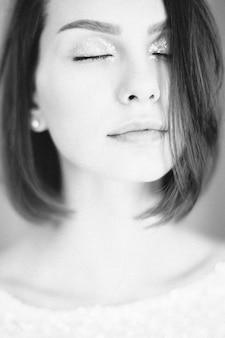 Retrato de mulher bonita, pensando com os olhos fechados na parte superior branca. preto e branco