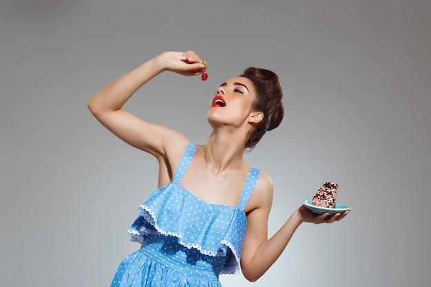 Retrato de mulher bonita pin-up comendo bolo