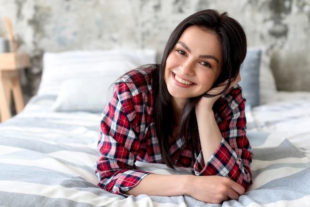 Retrato de mulher bonita posando na cama