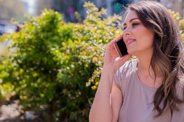 Retrato de mulher bonita que usa seu celular na