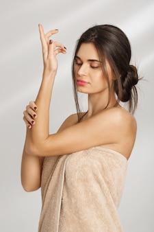 Retrato de mulher bonita relaxada, reparando as mãos com creme após spa usando cobertor