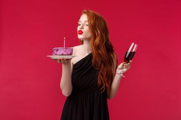 Retrato de mulher bonita ruiva feminina elegante com batom vermelho, maquiagem de noite e vestido preto, comemorando aniversário na festa com vinho tinto e bolo de aniversário, soprando velas sensualmente