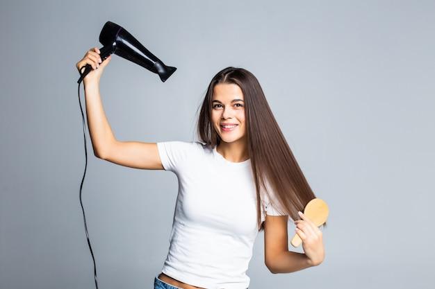 Retrato de mulher bonita, segurando o secador de cabelo isolado na cinza