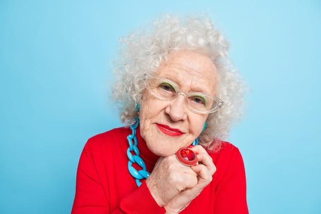 Retrato de mulher bonita sênior usando óculos grande anel de maquiagem brilhante parece com expressão satisfeita vestida com macacão vermelho