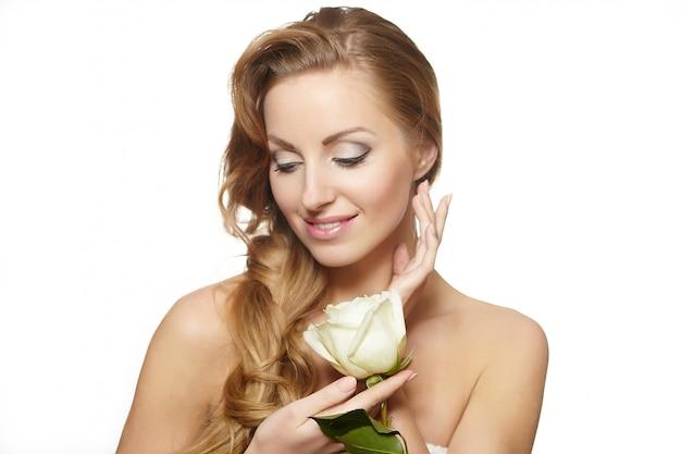 Retrato de mulher bonita sensual com rosa vermelha em cabelos cacheados longos de fundo branco, maquiagem brilhante