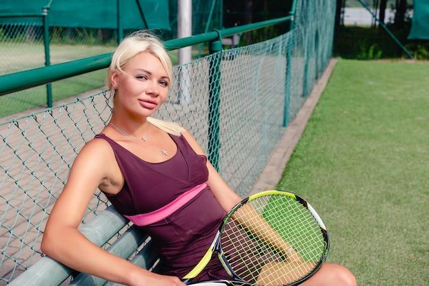 Retrato de mulher bonita sentada num banco depois de jogar tênis ao ar livre.