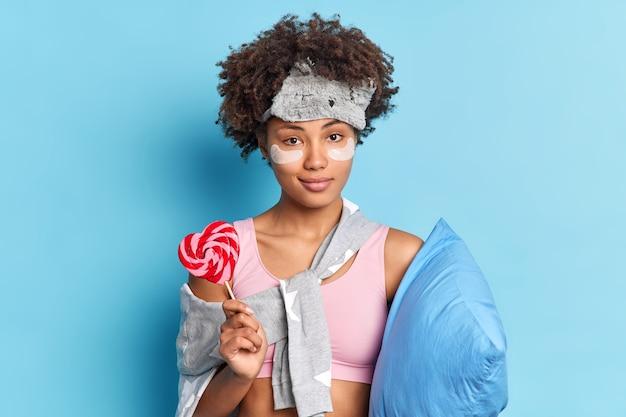 Retrato de mulher bonita séria e confiante segurando bala doce acorda após um sono saudável, vestida em poses de roupa de dormir com travesseiro contra a parede azul