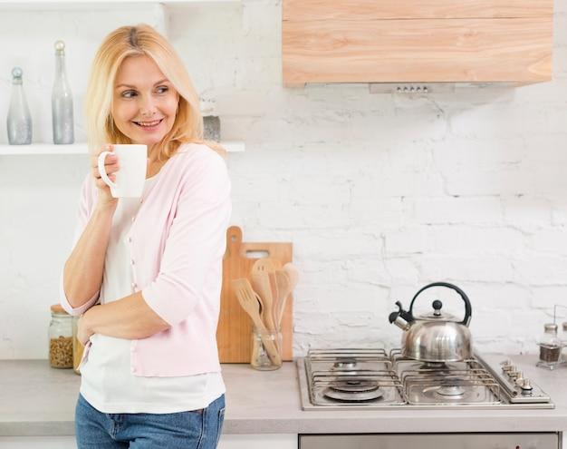 Retrato de mulher bonita, servindo café em casa