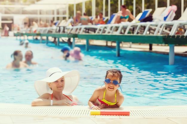 Retrato de mulher bonita sorridente e sua filha bonita em óculos de sol na piscina ao ar livre